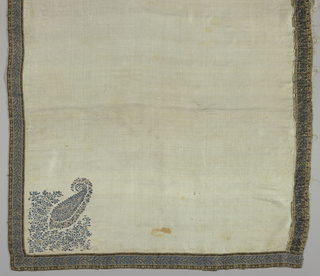 Small scarf or shawl of white silk with narrow border stitched on all edges. Border has stylized floral motifs in brown, blue, rose, yellow, and white. Field has a cone motif in blue and rose in one corner.