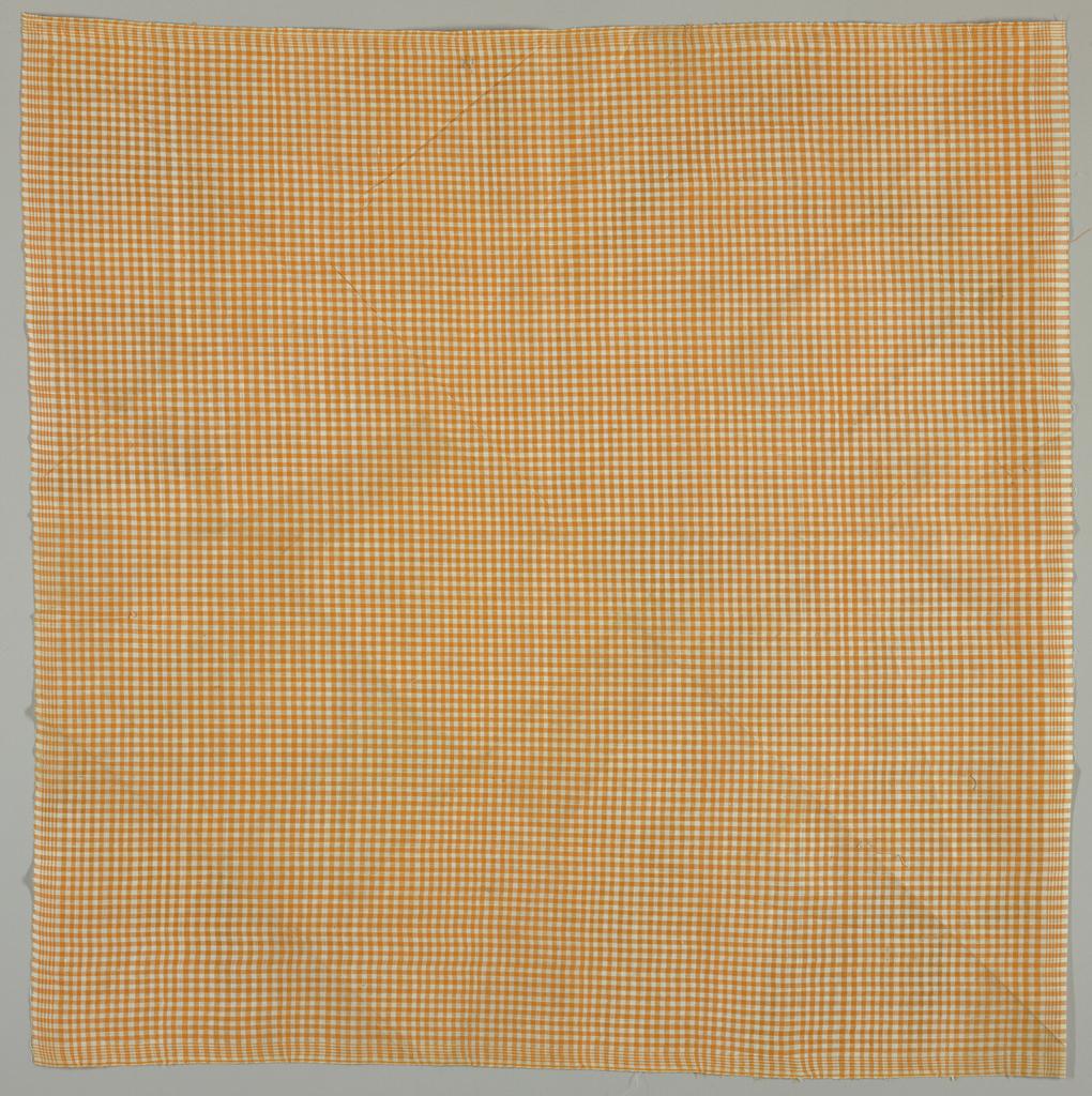 Unhemmed square of orange and white gingham.