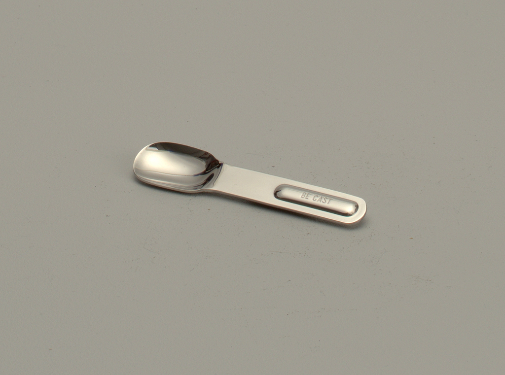 """Lozenge shaped polished steel form with oval bowl and """"BE CAST"""" on handle.  Part of six-piece picnic set."""