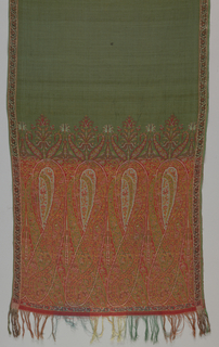 Machine-woven scarf with undecorated green field and a wide border at each end containing overlapping paisley cones in two shades of red, light blue, yellow-orange, olive green, and ivory. Floral vine border on each side runs the full length of scarf in dark green, dark red and ivory.