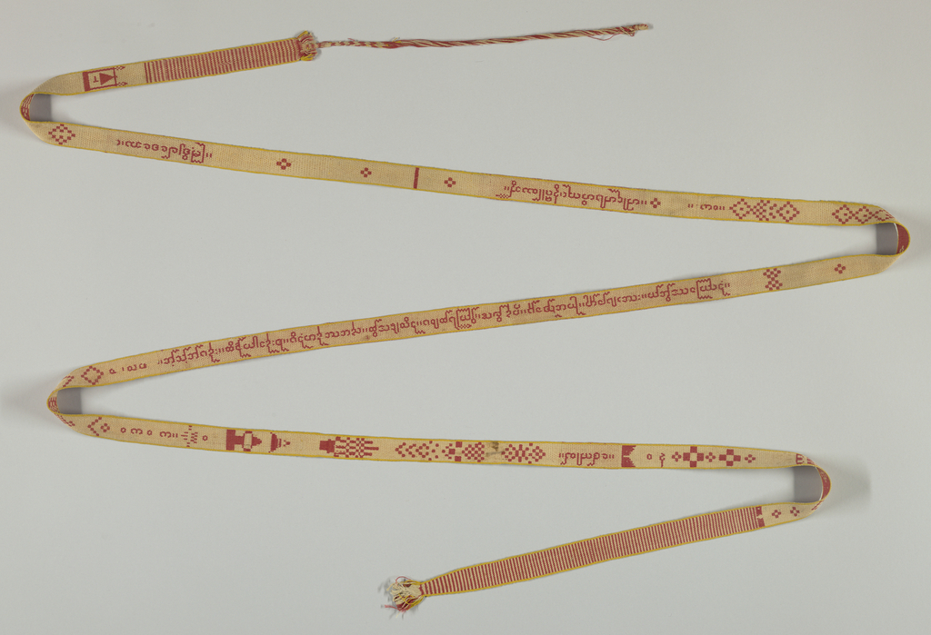 Geometrical ornament and inscription in the Pali language in red and cream. narrow saffron yellow edges or selvedges. Warp fringe (33cm) at one end.