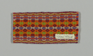 Card-woven belt fragment in a bird's eye pattern in orange, green, and shades of purple. Narrow, striped edges.