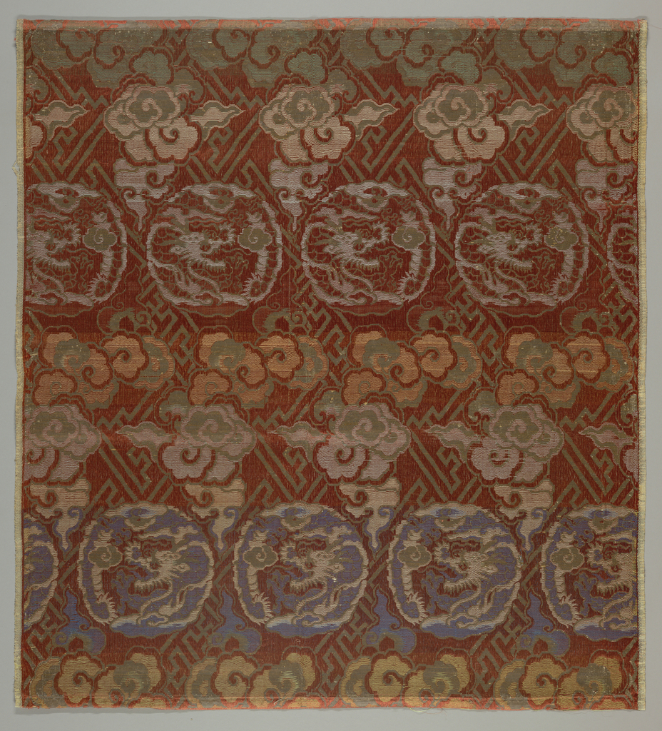 Gift cloth, or fukusa, with woven pattern of dragons in roundels and flowers arranged in horizontal bands on a fret ground. In shades of rose, blue, green, and gray with details in silvered paper. Lined with loosely woven cotton cloth.