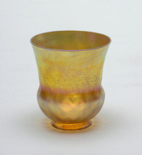 (a/e) Bell-shaped iridescent glass shade for sconce. Predominantly orange-gold. Diamond pattern formed in bulging part of bell shape. Plain round lip.