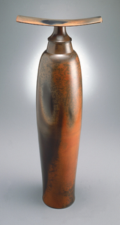 A tall and narrow vase in a varying brown color. Matching lid raises another piece of horizontal material (looking like a propeller).