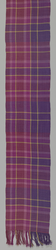 Silk scarf, handwoven by donor, tabby weave, in plaid' shades of red, purple, plum color, touches of yellow. Fringed of same silk.