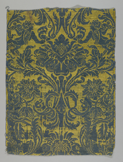 Formal pattern of a large ogee vine enclosing large blossoms. Pairs of winged figures are incorporated in the pattern. Blue pattern on a yellow ground.