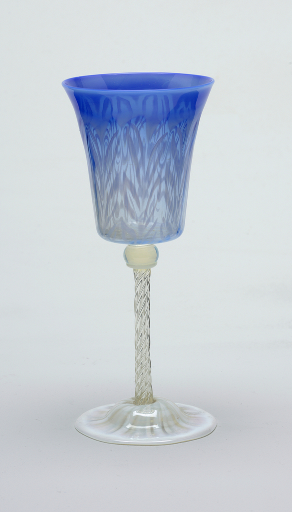 a&c) Inverted bell-shaped cups with deep blue upper portion and milky blue-white rims shading into clear glass; domed foot with white rim and eight white tapered pinwheel forms radiating form base of stems. b) The same except that milky blue-white forms more definite frame around leaf pattern on cup and arched foot is almost fully covered by whitish pinwheel design.