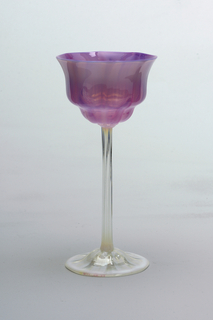 Flower-shaped cup with pink and mauve interiors shadowed on exteriors with milky white: fluted clear glass stems with milky white at top and bottom; domed foot with white rim and eight tapering pinwheel forms radiating from stem.