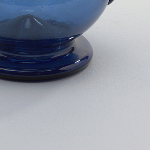 Dark blue glass vessel with long flaring neck and stout globular body; one handle of applied glass and long upturned spout.