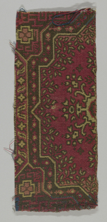 Small carpet fragment showing part of a large medallion repeat framing a rosette with geometrically decorated interspace, a debased derivation from Turkish rug. In red, yellow-green, orange, dark brown, dark blue, and pink.