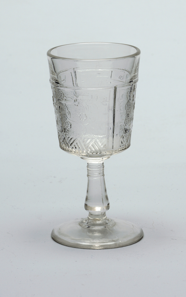 Clear glass.   Tapering cylindrical cup on flaring conical stem on stepped circular foot.  Cup molded with Japanese-inspired decoration of fret work, flowers, and flowing stems and leaves on a pebble-textured ground above a broad band of hatched lines.