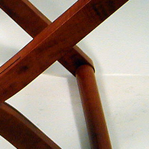 A pearwood folding stool with light brown leather seat and brass hardware.