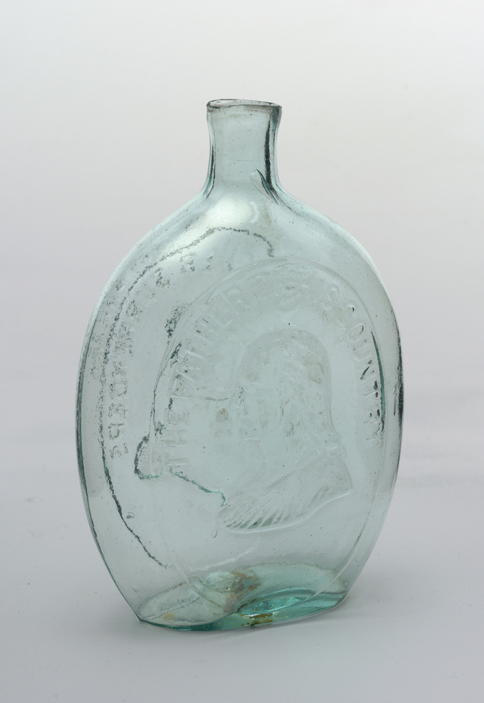 """Bottle green glass.  On one face, bust of Washington, with gueue, facing left. Inscription """"THE FATHER OF HIS COUNTRY"""". Reverse, bust of Taylor, in uniform, facing left. Inscription: """"GEN. TAYLOR NEVER SURRENDERS"""" """"DYOTTVILLE GLASSWORKS PHILAD.A."""" with sheared mouth.  Housing recommended"""