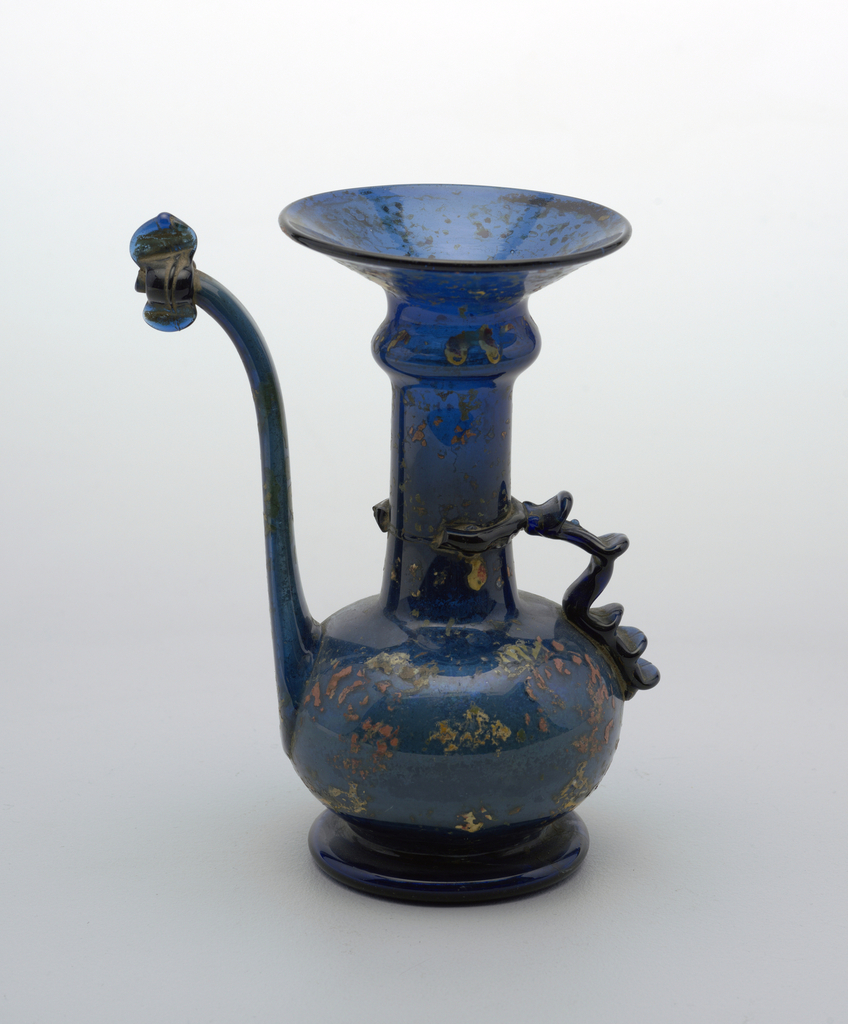 Blue glass with painted red and yellow decorations; Vessel with long cylindrical neck ,with horizontal rib, prounounced wide lip at top. Stout globlular  body; One handle of applied glass and long upturned spout.