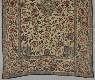 On dark cream ground, predominantly blue and red pattern of exotic flower heads and twining branches. Field has central medallion and decoration in each corner, is separated from wide floral border by two narrow decorated strips. Quilted and backed with coarse olive green and white cotton.