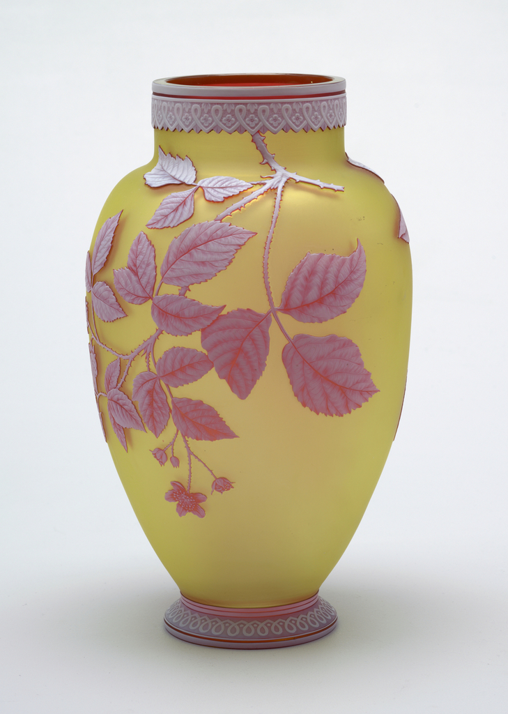 Ovoid body with wide straight neck and flared foot, both bearing etched bands of loop decoration in white to red overlay. Body bears a blackberry branch in white to red over lemon-yellow ground, and a spray of cherries in same colors.