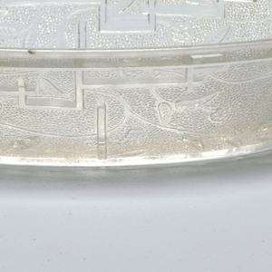 Of clear glass, the tapering oval form with simple slightly squared handles; outer surface of body molded with Japanese-inspired decoration of open flowers and flowing stems and leaves and fret work on a pebble-textured ground; underside of bottom with a regular pattern of squares.