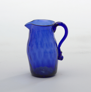 Cobalt blue creamer (crack in glass), blown and applied glass. Cobalt blue jug is expanded mold blown in a diamond lattice pattern, with flattened base and swelling curved sides tapering in toward and  outturned neck and lip. Scroll of handle of the glass applied with upper curve forming finger grips, lower portion of handle composed of pressed blobs and small scroll.. Pontil mark clearllly visible on underside.