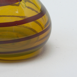 Gourd-shaped vase in yellow glass with maroon swirl.