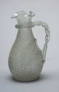 "Of clear ""ice"" or ""overshot"" glass, the rough-surfaced ovoid body tapering to slender neck flaring to mouth pinched to form wide spout; handle formed of spiral-textured rod looped around neck, twisted and attached to body below oval opening of indented well (for ice or other cooling agent)."
