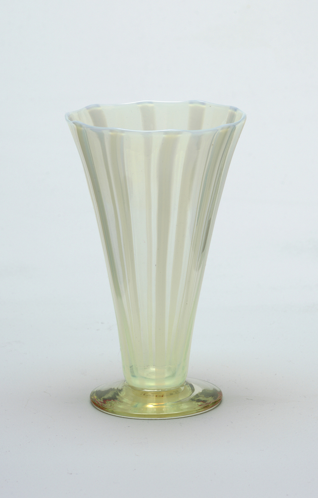Slightly yellow glass, pronounced yellow foot with vertical white glass.  Vessel has v-flaring shape