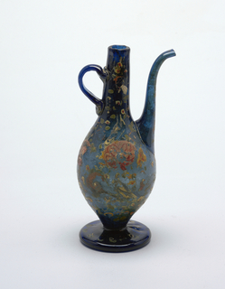 Blue glass footed pitcher with yellow and red painted decoration; pear-shaped vessel with semi-circular handle at neck.