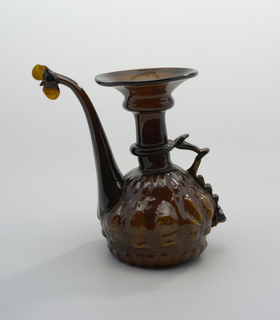 Brown Amber glass; Vessel with long flaring neck and slightly pear shaped body with tear drop shaped relief along base One handle of applied glass and long upturned spout; Pronounced slant