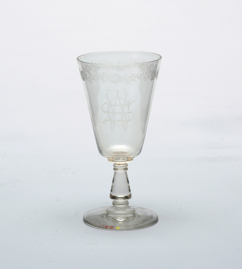 Slightly domed foot with baluster-shaped stem supporst straight-flaring bowl. Etched decoration, heightened by engraving. Floral wreath around top, and monogram W.C.S. (order (?) ) on side.