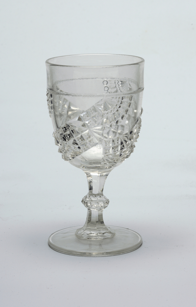 Clear glass.  Slightly tapering cylindrical cup curving to knoped faceted stem on flat circular foot.  Pressed decoration of diagonal bands of geometric patterns and folding fans on cup.