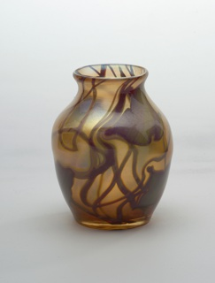 Ovoidal vase with rounded shoulder and everted lip; decorated with abstract floral pattern in dark red-black on gold background.