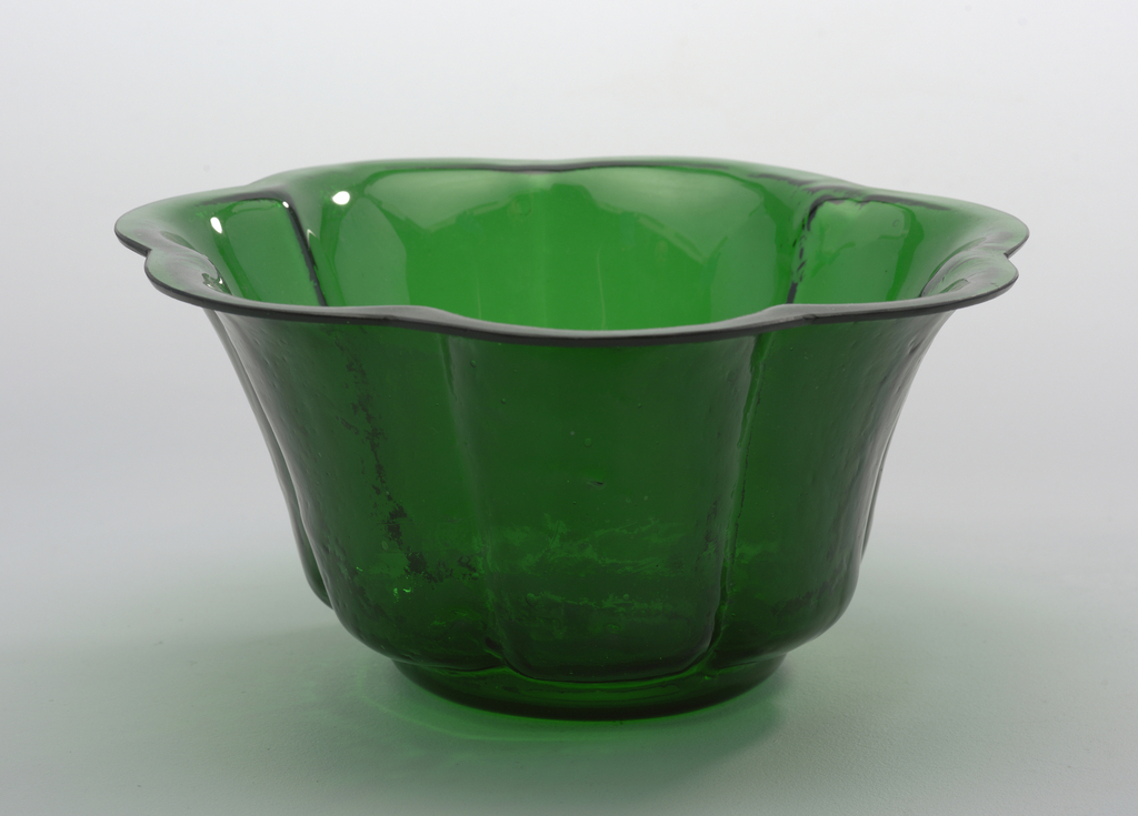 Tall-sided circular 7-lobed bowl with shaped rim; inside smooth, outer surface textured; green colored glass with slight blue cast