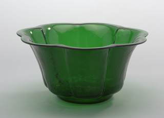 Tall-sided circular 7-lobed bowl with shaped rim; inside smooth, outer surface textured,; green colored glass with slight blue cast