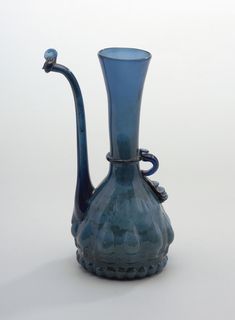 Blue glass vessel with long flaring neck and slightly pear shaped body with tear drop shaped relief along base and long upturned spout; handle of applied glass.