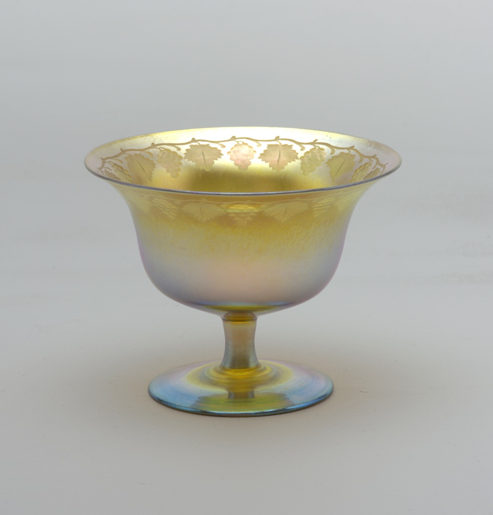 Spreading foot and short plain stem support bowl flaring to lip - iridescent - engraved band of symmetrical vintage mofits about inside upper margin.
