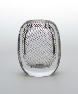 Thin black stripes suspended in thick clear glass vase