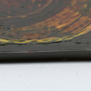 Green glass, yellow circle, brown infill, abstract design.
