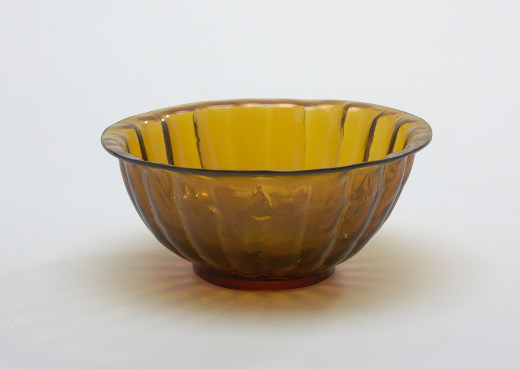 Mold-blown bowl of amber colored glass with an inverted rim, a ring foot, low and flat; sloping sides of radiating petal shaped flutes. Interior of bowl is smooth while glass on exterior is rough. Base polished flat, parallel striations on exterior sides.
