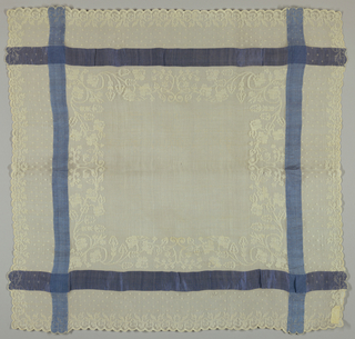 Square of piña cloth edged with wide border of floral motifs and a straight border in blue running along all four sides.