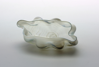 Roughly circular large bowl form of clear and white glass. One of 11 vessel forms of various sizes, reminiscent of sea creatures or sea shell forms. Vessels can be arranged in a variety of combinations.