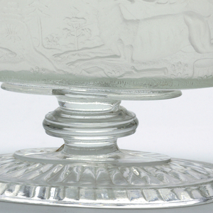 Compote with cover.  Oblong shape with frosted sides on colorless base; sides decorated with molded figures of buffalo and deer. Conforming lid is colorless glass surmounted by figure of a kneeling Indian