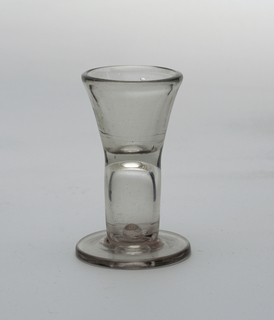 Flared form of thick, clear glass with flat foot. Large tear forms the base.