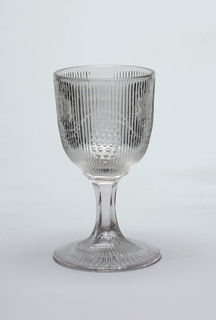Grape and vine decoration embedded into thin vertically ridged pattern on goblet.