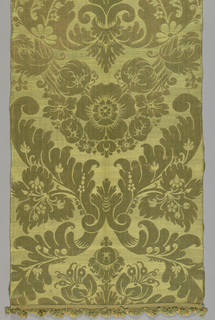 Gold ground patterned in leaf green with large symmetrical trophies of foliage and blossoms enclosed within ogives of boldly scrolling leaves and surmounting festoons of pomegranates centering on a cinquefoil.
