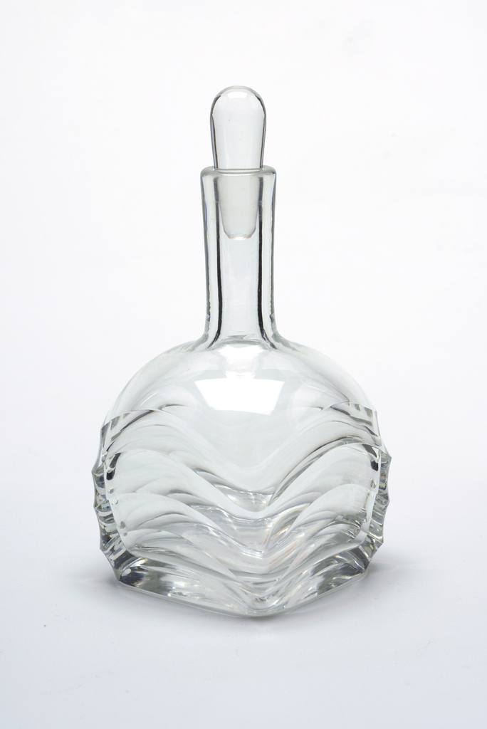 Molded glass decanter with stopper. Body decorated with a bold wave pattern.