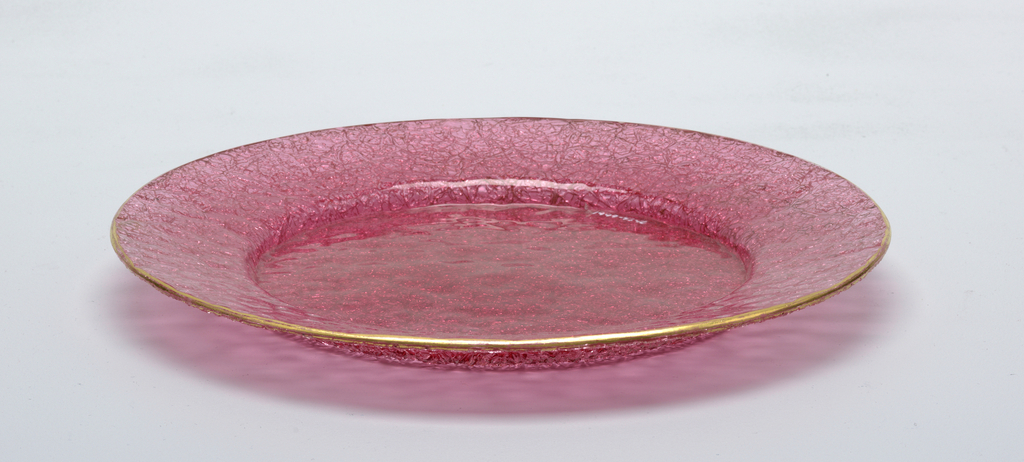 "Circular form of pink-red ""ice"" or ""overshot"" glass with wide rim and shallow well, smooth top surface, the underside rough and irregular; narrow gilded band around rim."