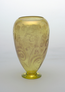 Yellow glass with maroon pattern.  Inverted egg shape on small circular foot.