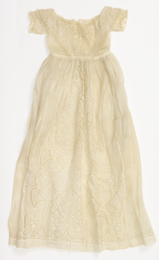 Bodice with low neck and revers forming collar at back; short sleeves; long full skirt. Front panel ornamented with medallions embroidered in pattern of rose buds joined with Valenciennes lace; embroidery and lace on revers, collar and sleeves; embroidery at bottom of skirt.
