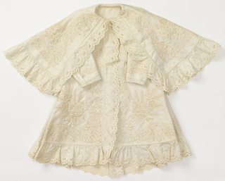 Child's coat with fitted bodice and full skirt, attached cape. Off-white ribbed cotton, heavily embroidered with white cotton in design of flowers and wheat. Edged with machine-embroidered ruffled cotton trimming.