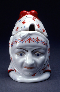 In the shape of the head of an old woman wearing a red and white kerchief; cover has slot for spoon at front center.